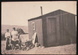 Randi Garmann and Tyra Schanche beside Randi' tar paper shack on her homestead