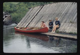 Three woman by canoe beside old wood structure, Sheyenne River, N.D.