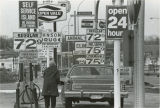 Woman pumping gasoline, University Drive S., Fargo, N.D.