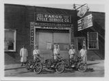 Fargo policemen by their motorcycles in front of Fargo Cycle Service Co.